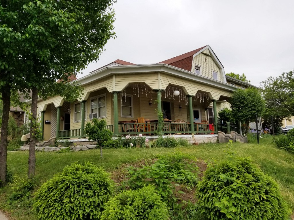 Image of Bloomington Cooperative Living's Middle Earth propety, a light yellow house with a wrap-around porch. In the foreground are trees and bushes.